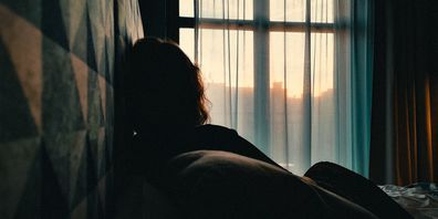 woman sitting on bed in front of window