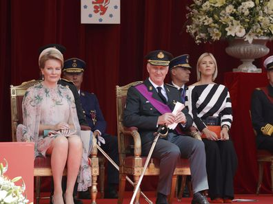 Belgium's Queen Mathilde, left, and Belgium's King Philippe, center, watch the National Day Parade from the podium in front of the Royal Palace in Brussels, Wednesday, July 21, 2021. Belgium celebrates its National Day on Wednesday in a scaled down version due to coronavirus, COVID-19 measures. (AP Photo/Olivier Matthys)