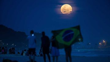 Locals watch the supermoon rise over Rio de Janeiro, Brazil. (Getty)
