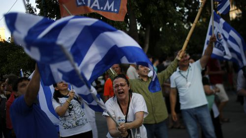 A supporter of the No vote waves a Greek flag after the referendum's exit polls at Syntagma square in Athens. (AAP)