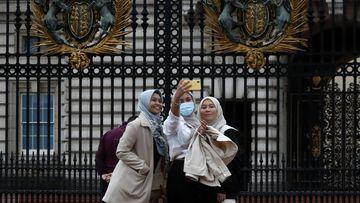 Tourists pose for selfies in front of the gates of Buckingham Palace in London.