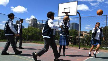Parramatta High School year 12 students play basketball on the school grounds.
