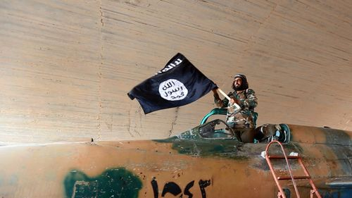 An Islamic State group fighter waves their flag from inside a captured government fighter jet following the battle for the Tabqa air base, in Raqqa, Syria. (AP Photo/ Raqqa Media Center of the Islamic State group)