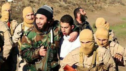 The man purported to be a Jordanian pilot (in white) with IS fighters. (AAP)