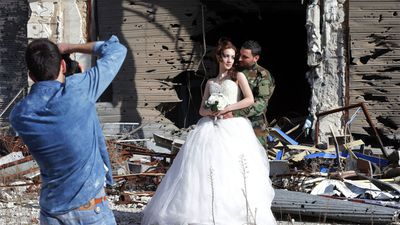 <p><strong>A Syrian army soldier and his new wife have posed for wedding photos against the backdrop of the war-ravaged city of Homs, once the centre of the nation's uprising against President Bashar al-Assad. </strong></p><p>(Joseph Eid/AFP/Getty)</p>