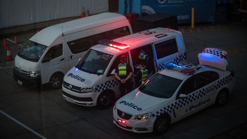 Members of Victoria Police are seen waiting at the International Terminal on January 27, 2021 in Melbourne, Australia.