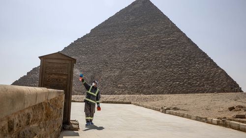 Municipal workers sanitize the areas surrounding the Giza pyramids complex in hopes of curbing the coronavirus outbreak in Egypt, Wednesday, March 25, 2020.