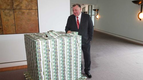 Independent MP Craig Kelly in front of a pallet of fake money.