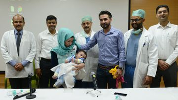 Iraqi parents Gufran Ali (3L) and Sarwed Ahmed Nadar (3R) pose with their eight month old son Karam (C) and physicians. (AFP)