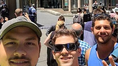 A group of friends took this selfie while standing behind police tape.