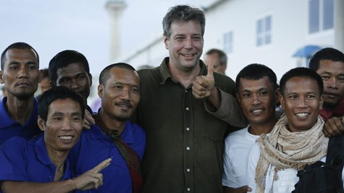 Unidentified sailors pose for a photograph with American writer Michael Scott Moore (C) who was also kidnapped but released in 2014. (AAP)