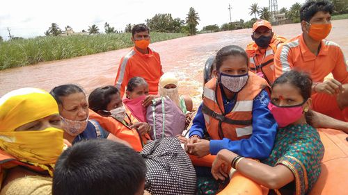 People stranded in flood waters watch others being rescued at Kolhapur in western Maharashtra state, India.