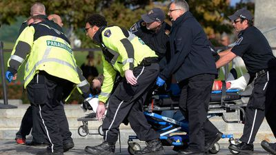 Paramedics treat one of the victims after the shootings across Ottawa. (AAP)
