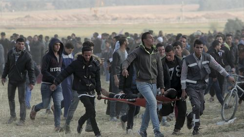 Palestinian protesters evacuate a wounded youth during clashes with Israeli troops along the Gaza Strip border with Israel. (AP)