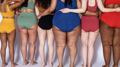 Rear view of group of women with different body type in underwear standing together on white background.