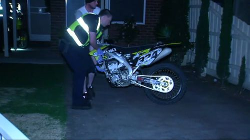 Officers seizing the motorbike.