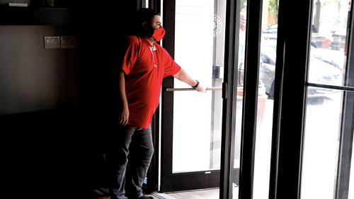 Wearing a mask amid concerns of the spread of the coronavirus, Dimitris Anagnostis opens the door to Chop House Burgers before the restaurant opened in downtown Dallas, Wednesday, July 8, 2020. (AP Photo/LM Otero)