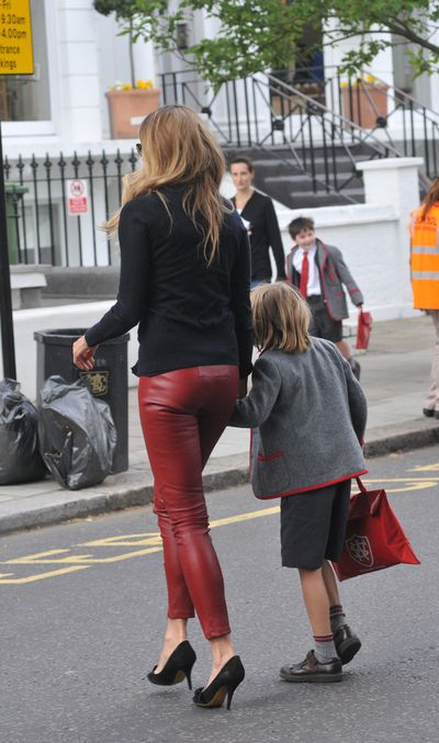 Elle Macpherson taking her son to school in Notting Hill in crimson leather pants.