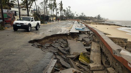 A car drives by a destroyed section of the road after Tropical Cyclone Idai, in Beira, Mozambique.