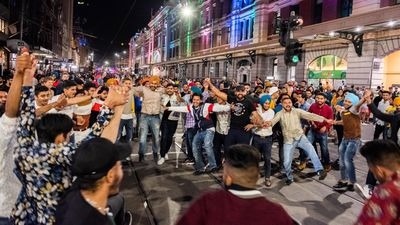 A group of men dancing outside Flinders street station during New Year's Eve celebrations on January 01, 2020 in Melbourne, Australia