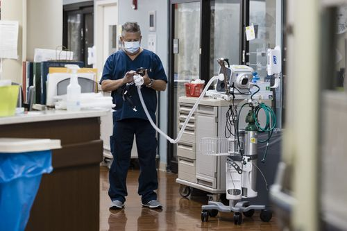 A healthcare worker holds an oxygen respirator tube in the Covid-19 Intensive Care Unit (ICU) at Freeman Hospital West in Joplin, Missouri, U.S., on Tuesday, Aug. 3, 2021. Hospitals in states where Covid-19 cases are once again surging are beginning to feel the strain in their emergency departments and intensive care units. Photographer: Angus Mordant/Bloomberg