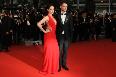 The usually scowly K.Stew turned up the vamp factor for Cannes. She looked stunning in red Reem Acra as she posed with her <i>On the Road</i> co-star Tom Sturridge.