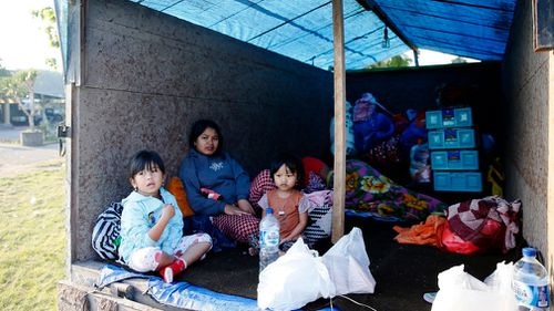 Residents stay at a temporary shelter as they evacuate from a dangerous area. (AAP)