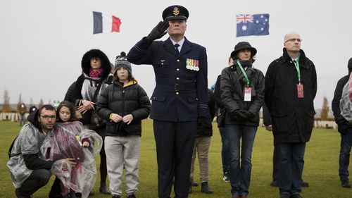 An Australian soldier listens along with visitors as French and Australian national anthems are played during an Armistice ceremony at the World War I Australian National Memorial in Villers-Bretonneux, France, Sunday, Nov. 11, 2018.