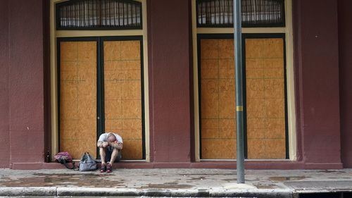 A man sits in front of a French Quarter business with windows boarded in preparation Hurricane Ida. (AP Photo/Eric Gay)