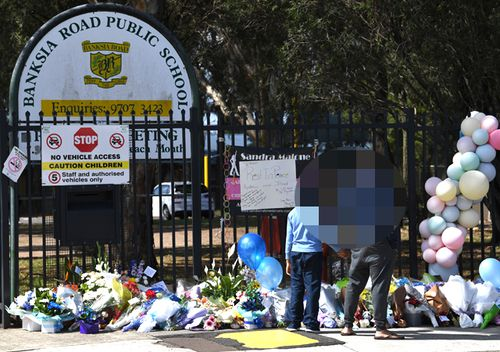 A father holds the hand of his son as they look at tributes laid outside the main entrance to Banksia Road Public School in Greenacre, Sydney, on November 8, 2017.