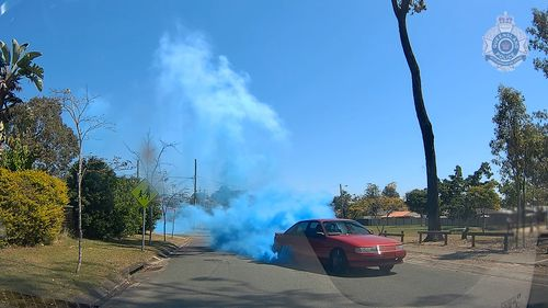 Dashcam footage shows a red Holden Commodore VP performing burnouts, with blue smoke coming from its tyres.