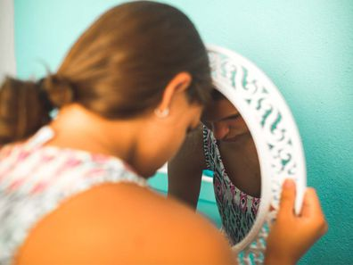 A teenage girl toucher head to the mirror looking sad
