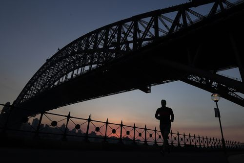 A jogger runs along Sydney Harbour under the Sydney Harbour Bridge against the backdrop of a stunning sunrise created by smoke haze from hazard reduction burns in Sydney. (AAP)