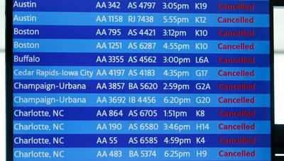 A digital board shows flight cancellations at Terminal 3 at O'Hare International Airport in Chicago, Illinois.