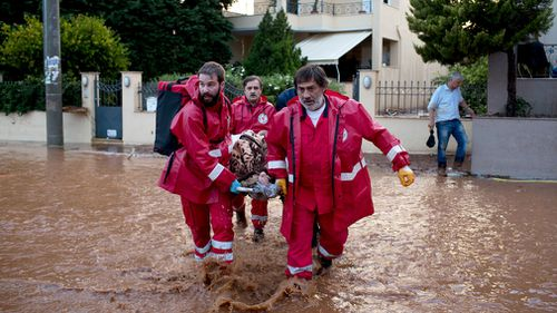 Red Cross personnel and a firemen carry an elderly man to the ambulance in the municipality of Mandra, western Athens. (AAP)