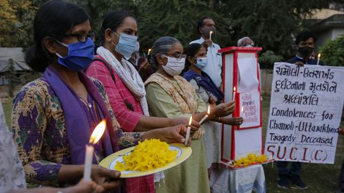 Activists of Socialist Unity Center of India (SUCI) light candles in Ahmedabad, India, for the victims of glacier flooding in the northern state of Uttarakhand.
