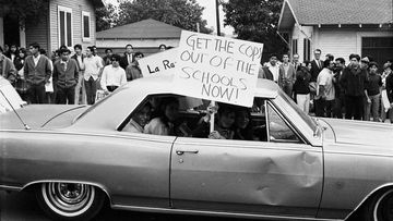 """This March 1968 photo provided by the UCLA Chicano Studies Research Centre, protesters in a car drive by with a sign that reads """"Get the Cops Out of the Schools Now!"""" during a walkout by students at Theodore Roosevelt High School in Los Angeles."""