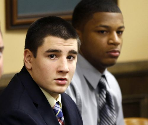 High school quarterback Trent Mays, 17, and 16-year-old wide receiver Ma'lik Richmond sit at the defence table before the start of their trial on rape charges in juvenile court, Ohio.