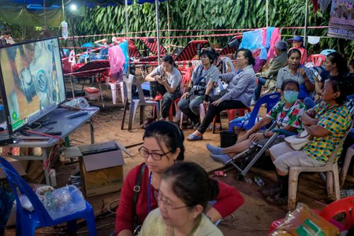 Families huddle around a TV at the makeshift camp at Khun Nam Nang Non Forest Park, as they wait for news on the 12 boys and their coach. (Getty)