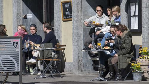 People sit outside in the sun in a coffee bar in central Stockholm, Sweden, on Saturday.