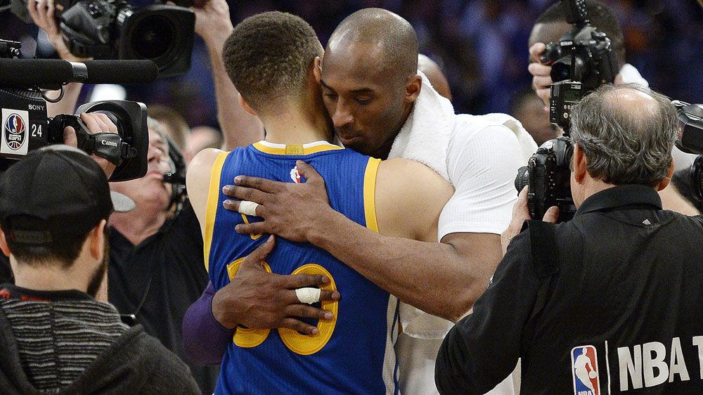 Kobe Bryant (R) embraces Steph Curry after their clash. (Getty)