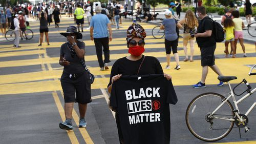 Nickia Wood stands with a Black Lives Matter shirt as people gather near the White House, Saturday, June 6, 2020