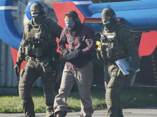 Photographs showed a blindfolded man being led by police to a helicopter.