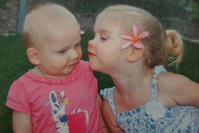 Big sister Elle kisses Elaina whom she adored.