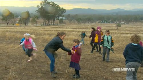 Locals dance in the rain, even if it was short lived. 10mm fell in Tamworth - it's the most rain they've had in six months. Picture: 9NEWS