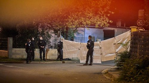 Police guard the scene where police shot a man after he decapitated a middle school teacher and posted the act on social media on October 16, 2020 in Conflans-Sainte-Honorine, France