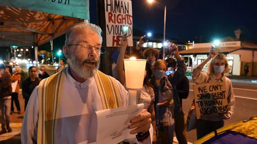 Father Denis Scanlan (left) and protestors are seen outside the Kangaroo Point Central Hotel in Brisbane, Friday, June 12, 2020