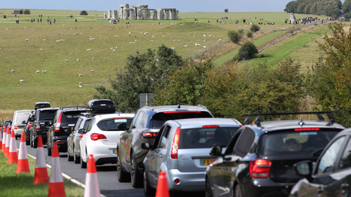 Traffic builds up on the main road near Stonehenge, seen in background, as people try to get away for the holiday weekend, Friday Aug. 28, 2020. (Andrew Matthews/PA via AP)