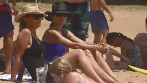 Princess Mary, in a royal blue swimsuit, chats to a friend in the sun.