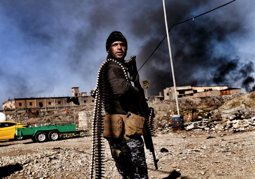 Smoke rises in the background as members of Iraq's elite Rapid Response Division hold position in the northern city of Mosul, on February 25, 2017. (AFP)
